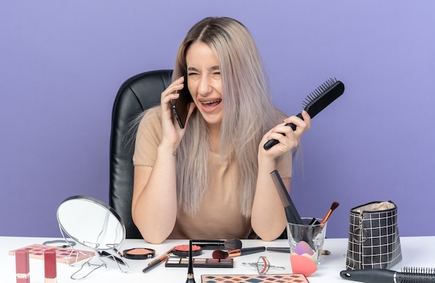 Lachende jonge, mooie meid met een beugel zit aan tafel met make-uptools spreekt op een telefoon met een kam geïsoleerd op een blauwe muur