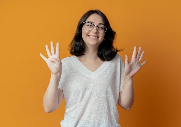 Lachende jonge mooie vrouw draagt een bril met negen met handen