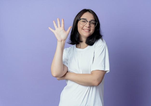 Lachende jonge mooie vrouw draagt een bril met vijf met de hand
