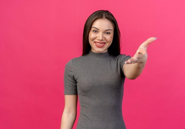 Lachende jonge mooie vrouw hand strekken op camera geïsoleerd op roze met kopie ruimte