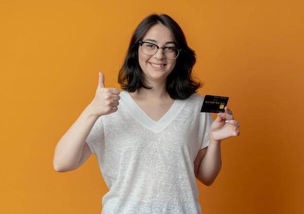 Lachende jonge mooie vrouw met bril duim opdagen en creditcard bedrijf
