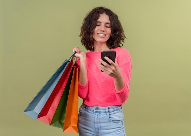 Lachende jonge mooie vrouw met kartonnen zakken en mobiele telefoon op geïsoleerde groene muur met kopie ruimte