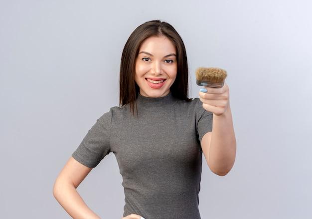 Lachende jonge mooie vrouw verf penseel uitrekken op camera en hand zetten taille geïsoleerd op een witte achtergrond met kopie ruimte