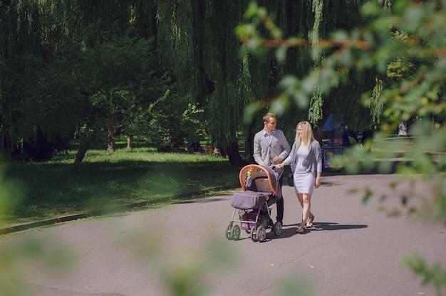 Lachende jonge ouders wandelen met hun baby