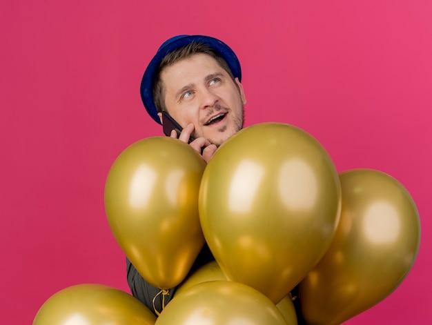 Lachende jonge partij man met blauwe hoed achter ballonnen spreekt op telefoon geïsoleerd op roze