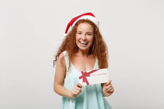 Lachende jonge roodharige santa meisje in lichte kleding, kerstmuts geïsoleerd op een witte achtergrond in de studio. gelukkig nieuwjaar 2020 viering vakantie concept. bespotten kopie ruimte. cadeaubon houden.