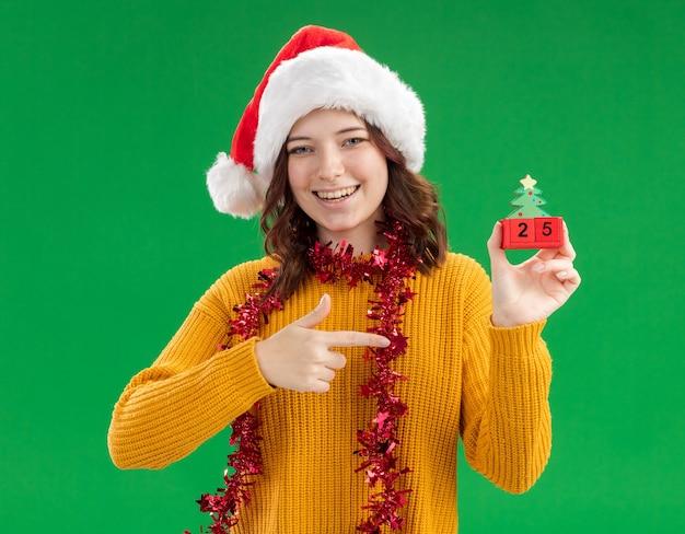 Lachende jonge slavische meisje met kerstmuts en met slinger om nek houden en wijzend op kerstboom ornament geïsoleerd op groene muur met kopie ruimte