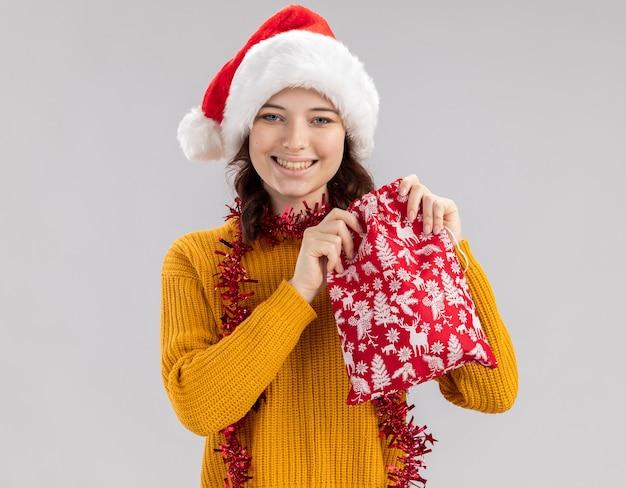 Lachende jonge slavische meisje met kerstmuts en met slinger om nek houden kerstcadeau tas geïsoleerd op een witte muur met kopie ruimte