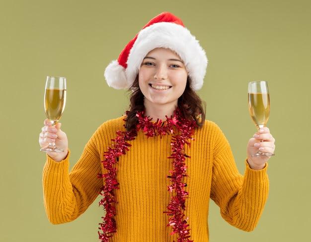 Lachende jonge slavische meisje met kerstmuts en met slinger om nek met glazen champagne geïsoleerd op olijfgroene achtergrond met kopie ruimte