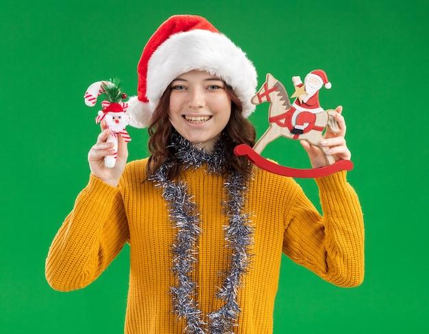 Lachende jonge slavische meisje met kerstmuts en met slinger om nek met snoepgoed en santa op hobbelpaard decoratie geïsoleerd op groene muur met kopie ruimte