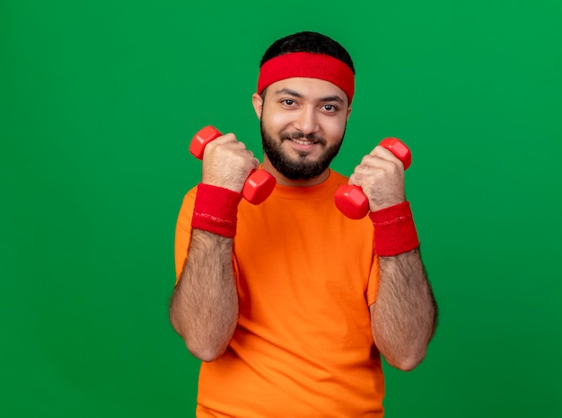 Lachende jonge sportieve man met hoofdband en polsband trainen met halters geïsoleerd op een groene achtergrond