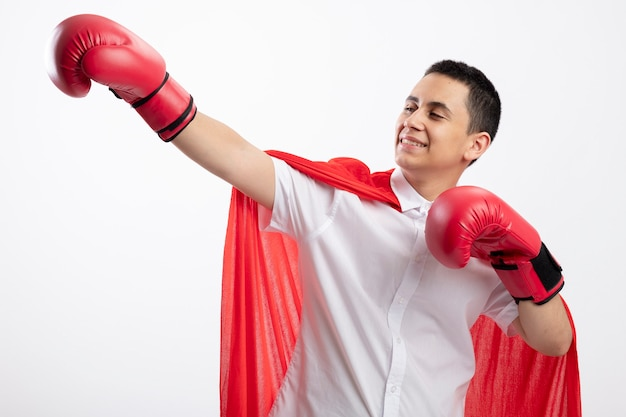 Lachende jonge superheld jongen in rode cape doos handschoenen strekken hand houden een andere in de lucht kijken kant geïsoleerd op een witte achtergrond
