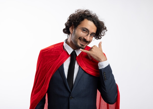 Lachende jonge superheld man in optische bril dragen pak met rode mantel gebaren bel me teken geïsoleerd op een witte muur