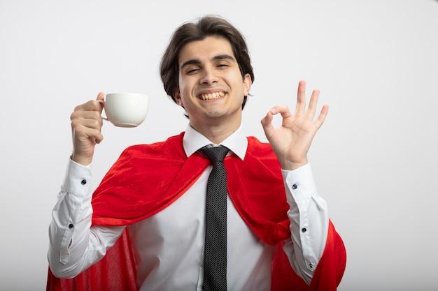 Lachende jonge superheld man met gesloten ogen dragen stropdas kopje thee houden en tonen ok gebaar geïsoleerd op een witte achtergrond
