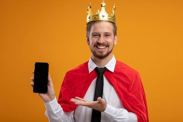 Lachende jonge superheld man met stropdas en kroon bedrijf en punten met de hand op de telefoon geïsoleerd op een oranje achtergrond