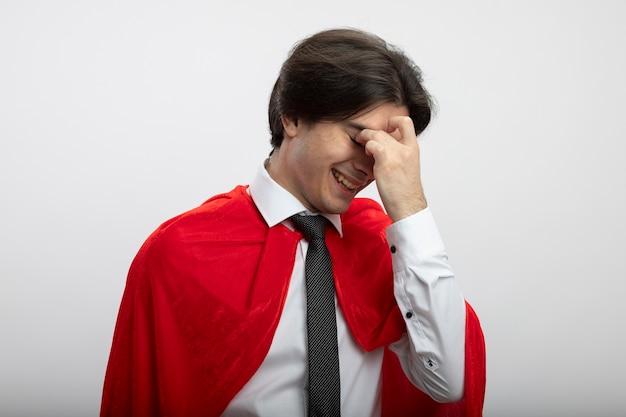 Lachende jonge superheld man met verlaagd hoofd dragen stropdas afvegende ogen met hand geïsoleerd op een witte achtergrond