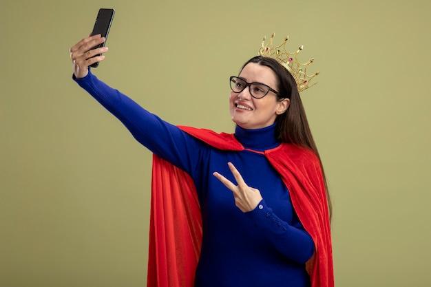 Lachende jonge superheld meisje bril en kroon tonen vredesgebaar neem een selfie geïsoleerd op olijfgroene achtergrond