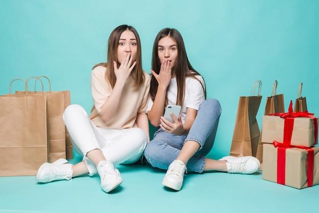 Lachende jonge twee meisjes zitten vloer boodschappentassen en geschenken geschokt turquoise muur.