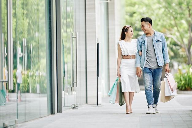 Lachende jonge vriend en vriendin met boodschappentassen wandelen in de straat met boodschappentassen