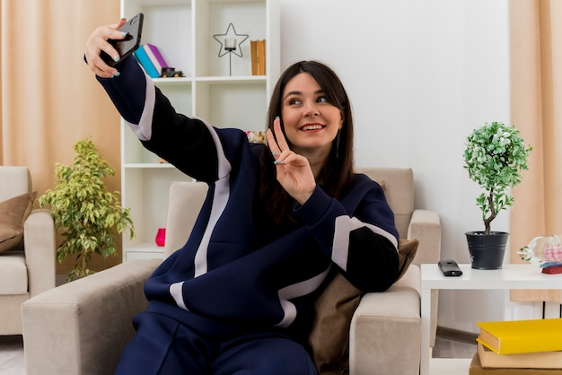 Lachende jonge vrij kaukasische vrouw zittend op een stoel in ontworpen woonkamer vredesteken doen en selfie te nemen
