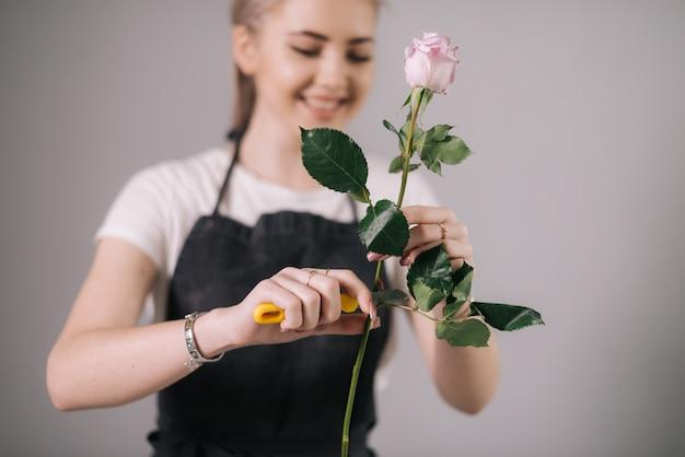 Lachende jonge vrouw bloemist met schort snijdt verse roze bloem met een schaar