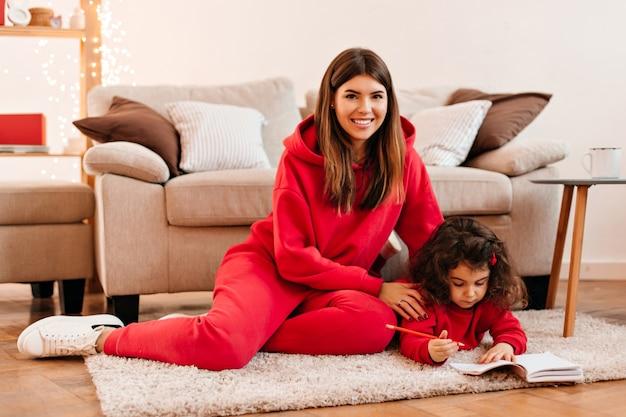 Lachende jonge vrouw die dochter onderwijst om te schrijven. binnen schot van gelukkige moeder en kind zittend op een tapijt.