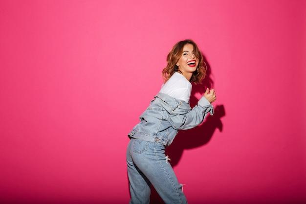Lachende jonge vrouw die over roze wordt geïsoleerd