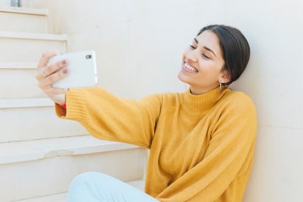 Lachende jonge vrouw die selfie op mobiele telefoon