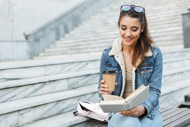 Lachende jonge vrouw draagt jas zittend op een bankje buitenshuis, boek lezen, kopje afhaalmaaltijden koffie te houden