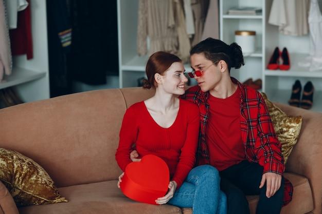 Lachende jonge vrouw en man met valentijnsdag geschenkdoos rood hart gevormd thuis bank.