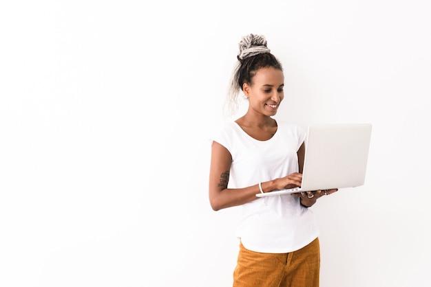 Lachende jonge vrouw, gekleed in casual outfit staande geïsoleerd op wit, met behulp van laptop computer