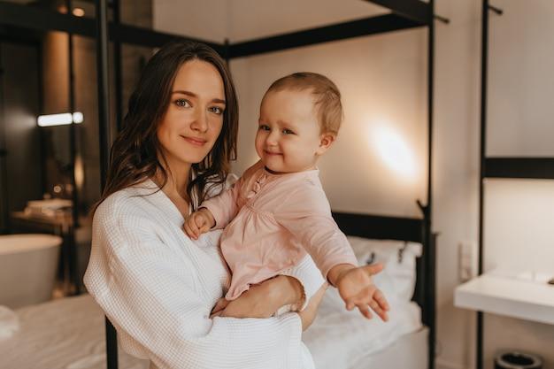 Lachende jonge vrouw in badjas en haar schattige baby dochter glimlachend en poseren in de slaapkamer.