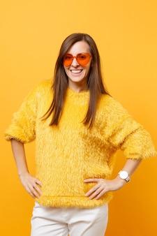 Lachende jonge vrouw in bont trui, witte broek en hart oranje bril permanent met armen akimbo geïsoleerd op heldere gele achtergrond. mensen oprechte emoties, lifestyle concept. reclame gebied.