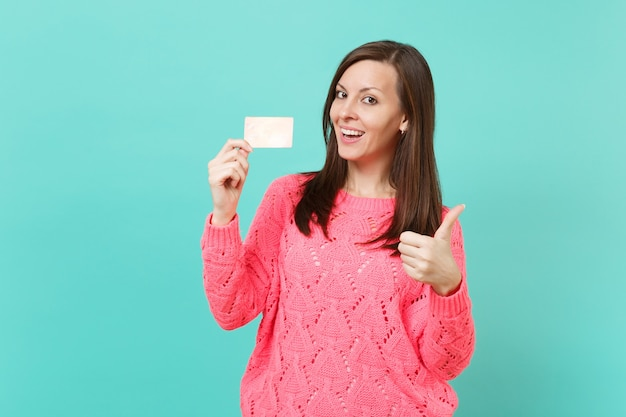 Lachende jonge vrouw in gebreide roze trui duim opdagen en creditcard in de hand houden geïsoleerd op blauwe turquoise muur achtergrond studio portret. mensen levensstijl concept. bespotten kopie ruimte.
