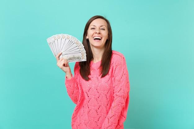 Lachende jonge vrouw in gebreide roze trui in de hand houden veel bos dollars bankbiljetten, contant geld geïsoleerd op blauwe muur achtergrond, studio portret. mensen levensstijl concept. bespotten kopie ruimte.