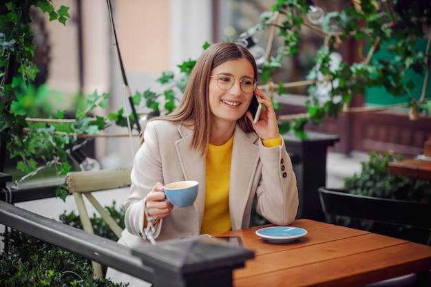 Lachende jonge vrouw in gele trui zittend op het terras van cafetaria, kopje koffie houden en praten over een telefoon.