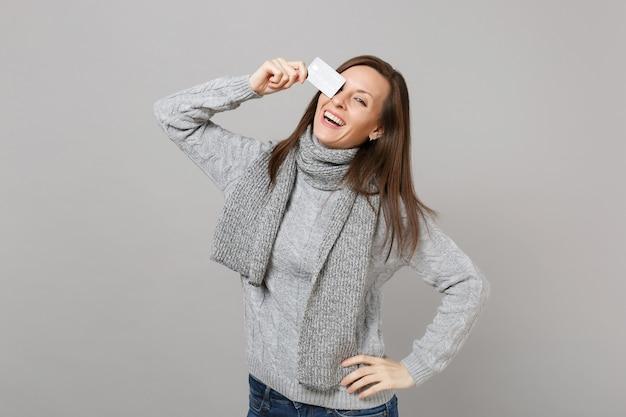 Lachende jonge vrouw in grijze trui, sjaal die oog bedekt met creditcard geïsoleerd op een grijze achtergrond. gezonde mode-levensstijl, oprechte emoties van mensen, concept van het koude seizoen. bespotten kopie ruimte.