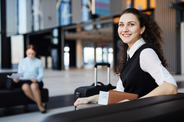 Lachende jonge vrouw in luchthaven