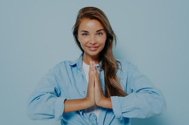 Lachende jonge vrouw in oversized shirt en wit t-shirt geïsoleerd op blauwe studio achtergrond hand in hand in gebed namaste gebaar, dankbare vrouw kijkt naar camera voel dankbaar