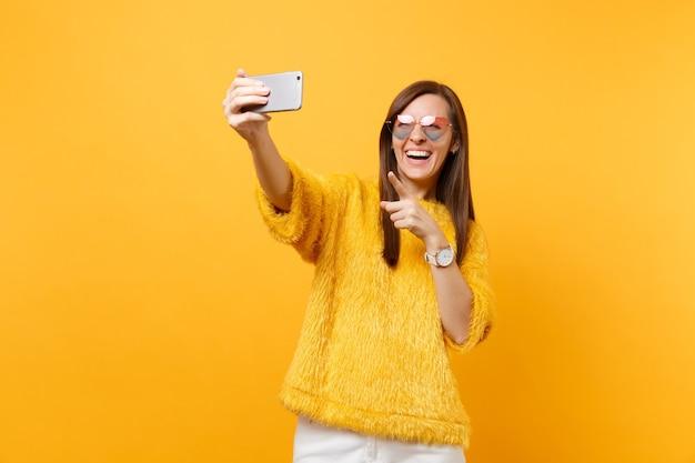 Lachende jonge vrouw in trui hart bril doen selfie schot op mobiele telefoon wijzende wijsvinger geïsoleerd op heldere gele achtergrond. mensen oprechte emoties, levensstijl. reclame gebied.