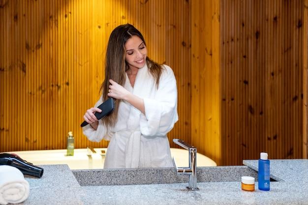 Lachende jonge vrouw in witte badjas lang haar borstelen terwijl je in de buurt van wastafel in badkamer met houten interieur