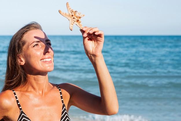 Lachende jonge vrouw is bedekt met een zeester van de zon op de achtergrond van de zee.