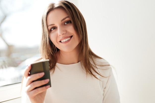 Lachende jonge vrouw koffie drinken uit papieren beker