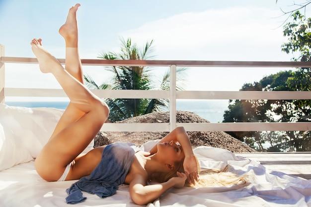 Lachende jonge vrouw met mooie benen rusten op een zonnige dag