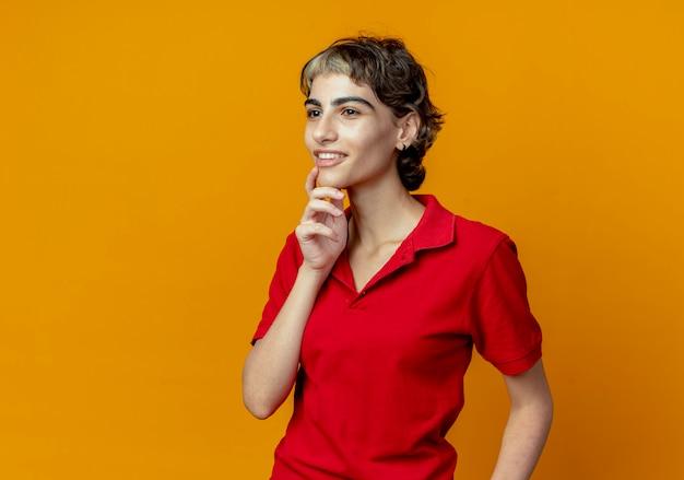 Lachende jonge vrouw met pixie kapsel aanraken kin op zoek recht