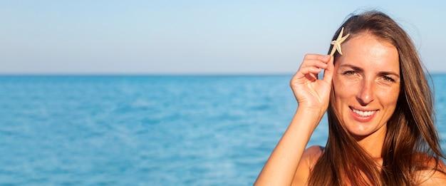 Lachende jonge vrouw met zeester op de achtergrond van de zee. banier.