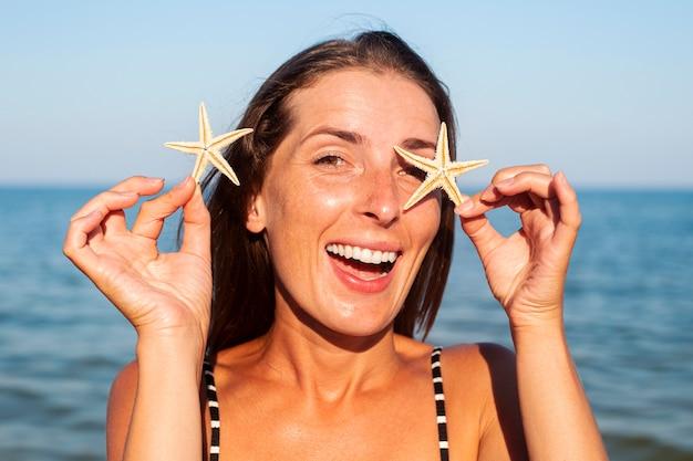 Lachende jonge vrouw met zeester op de achtergrond van de zee.