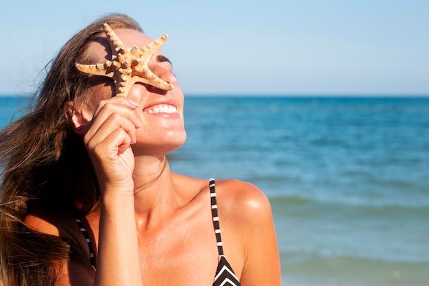 Lachende jonge vrouw met zeester sluit haar oog met zeester op de achtergrond van de zee.