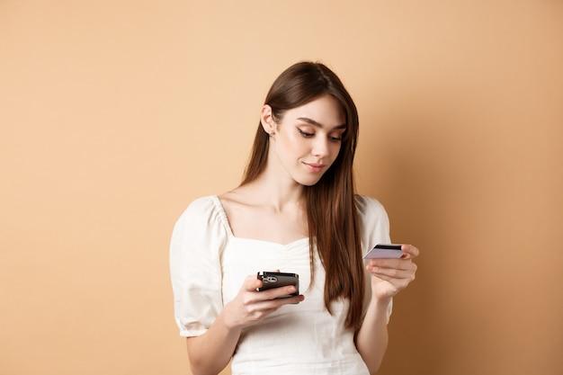 Lachende jonge vrouw online betalen, creditcard kijken en aankopen doen op de mobiele telefoon, winkelen op internet, staande op beige.