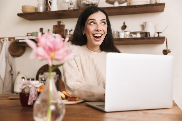 Lachende jonge vrouw ontbijten zittend in de keuken en laptopcomputer gebruikt